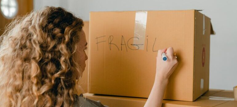 A woman writing fragile on a box
