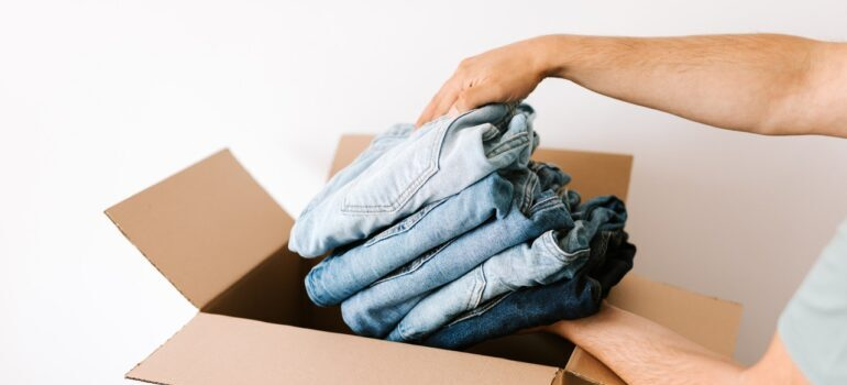 A person putting clothes in a box