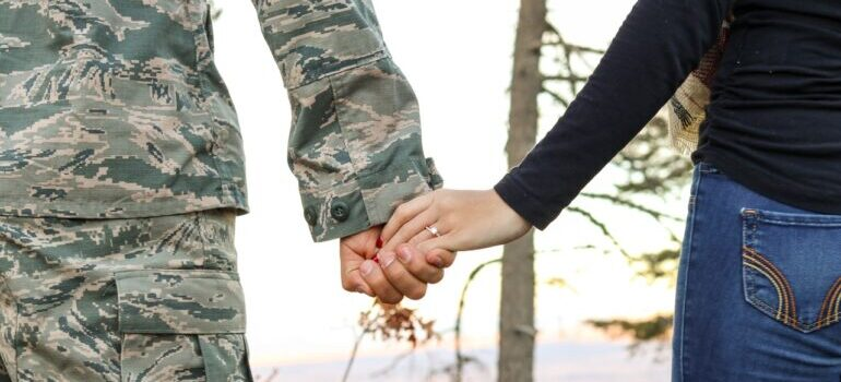 A soldier and a woman holding hands